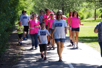 Youth Impact kids bring their bright pink enthusiasm to support walkers and join in the fun.
